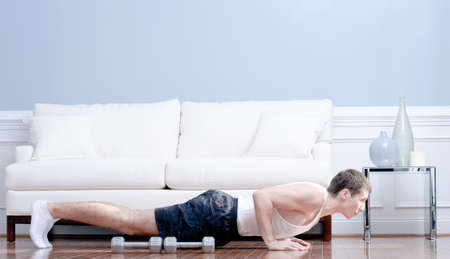 Full length view of man doing push-ups next to couch, with arm weights lying next to him. Horizontal format.