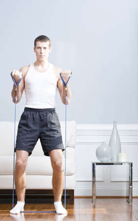Man standing and using resistance bands in his living room. Vertical format.