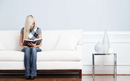 Full length view of woman sitting on a white couch with a book. Horizontal format. photo