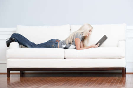 Full length view of woman lying on white couch and reading a book. Horizontal format.