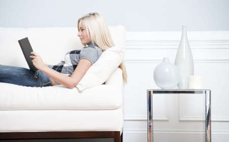 Cropped view of a woman relaxing on a white couch and reading a book. Horizontal format.