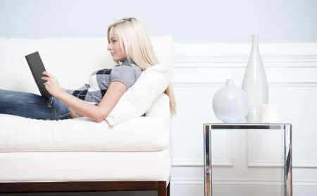 Weergave van een vrouw ontspannen op een witte bank bijgesneden en een boek lezen. Horizontale indeling.  Stockfoto - 6248341