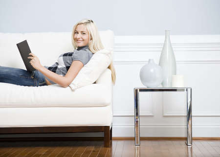 woman on couch: Cropped view of a woman relaxing on a white couch with a book and smiling at the camera. Horizontal format.