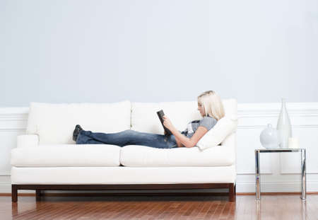 Full length view of woman reclining on white couch and reading a book. Horizontal format. photo