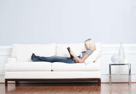 Full length weergave van de vrouw op witte laag achterover en een boek lezen. Horizontale indeling.  Stockfoto - 6248796