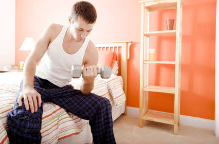 Cropped view of man sitting on bed and using an arm weight. Horizontal format.