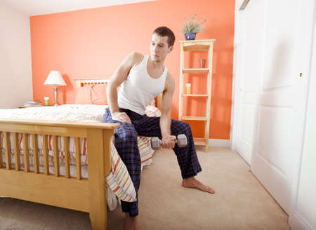 Full length view of man sitting on bed with a blank expression and using an arm weight. Horizontal format. photo