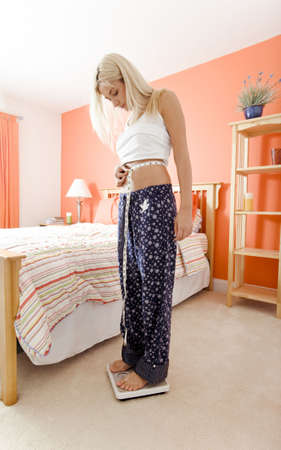 Woman standing on a scale next to her bed and using a tape measure to measure her waist. Vertical format. photo