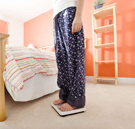 Cropped view of woman standing on a scale next to her bed. Square format. photo