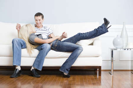Smiling couple together on white couch, with woman reclining with her head in the man's lap. Horizontal format.