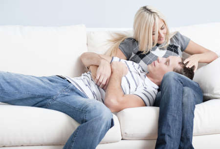 couple on couch: Couple relaxing on couch, with man lying with his head in the womans lap. Horizontal format.