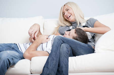 Laughing couple relaxing on couch, with man lying with his head in the womans lap. Horizontal format. photo
