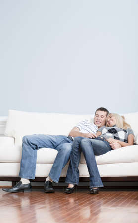 couple on couch: Full length view of affectionate couple laughing and relaxing together on white couch. Vertical format.