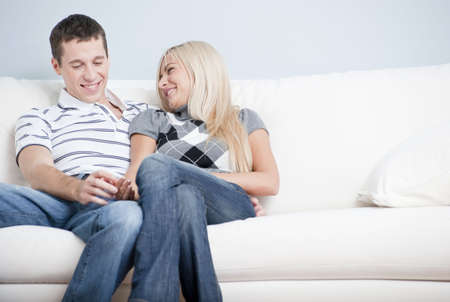 couple on couch: Cropped view of affectionate couple laughing and relaxing together on white couch. Horizontal format. Stock Photo
