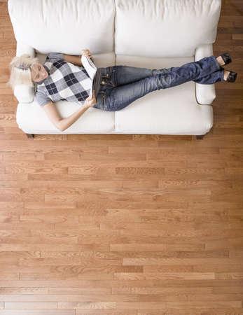 calm down: Lunghezza totale overhead view of woman reclinabili e leggendo sul divano bianco. Formato verticale.