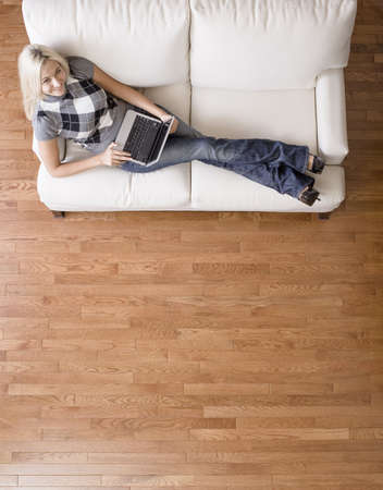 Full length overhead view of woman smiling up at the camera as she reclines on a white couch with a laptop. Vertical format.