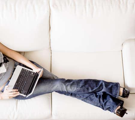 흰 소파에 reclining 및 랩톱을 사용하는 여자의 오버 헤드보기를 잘립니다. 가로 형식입니다.