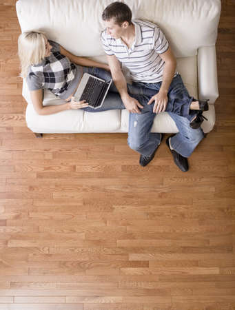 Full length overhead view of couple relaxing together on white couch, with woman using laptop and stretching out with her legs in the man's lap. Vertical format. Stock Photo - 6249358