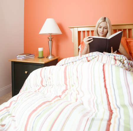 nightstand: Blonde woman sitting in bed and reading a book. Square format.