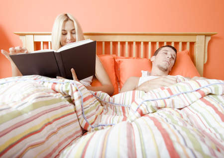 View of couple in bed, with woman reading book and man sleeping. Horizontal format. Stock Photo - 6248635