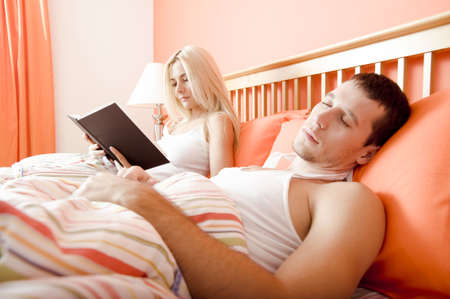 View of couple in bed, with woman reading book and man sleeping. Horizontal format. photo