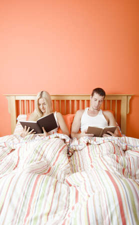 Man and woman reading side-by-side in bed. Vertical format. photo