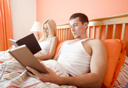 Man and woman reading side-by-side in bed. Horizontal format. photo