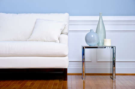 Cropped view of white couch and side table with vases, in a living room with a wood floor. Horizontal format. Stock Photo