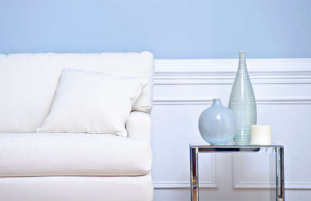 Cropped view of a living room, focusing on a white couch and side table with vases. Horizontal format. Stock Photo