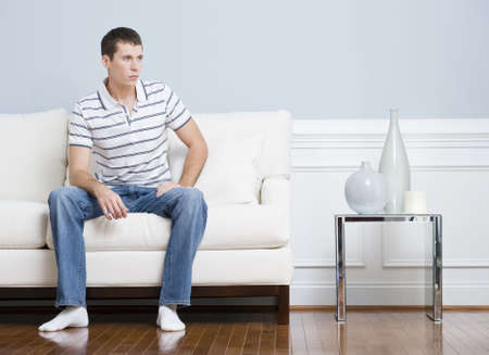 Man in casual clothing sitting on a white couch in a living room. He has a blank expression and is looking to the side. Horizontal format.