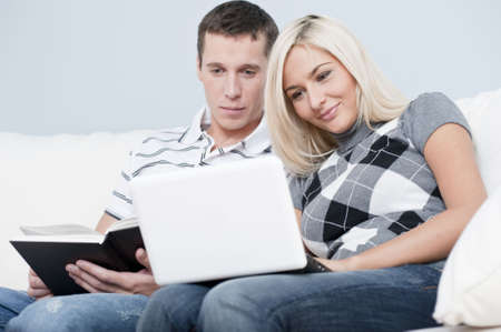 Man is reading, and woman is using a laptop, as they sit side by side on a white couch. Horizontal format. photo