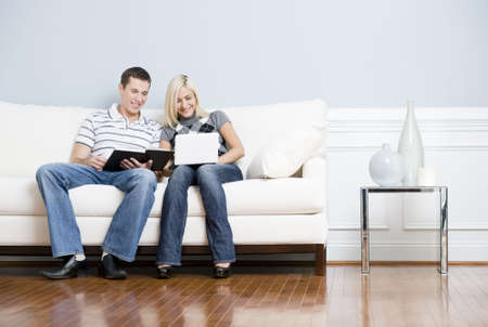 Man is reading, and woman is using a laptop, as they sit side by side on a white couch. Horizontal format. 스톡 콘텐츠