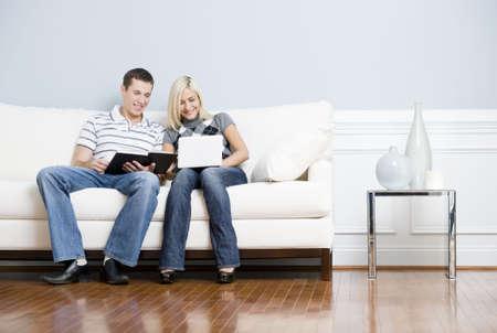 Is het lezen van man en vrouw is het gebruik van een laptop, als ze naast elkaar op een witte bank zitten. Horizontale indeling. Stockfoto