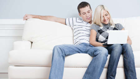 Man and woman sit side by side on a white couch. The woman is using a laptop, and the man is snuggling next to her. Horizontal format.