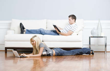 Man reads on a couch while woman stretches out on the floor with her laptop. Horizontal format. 스톡 콘텐츠