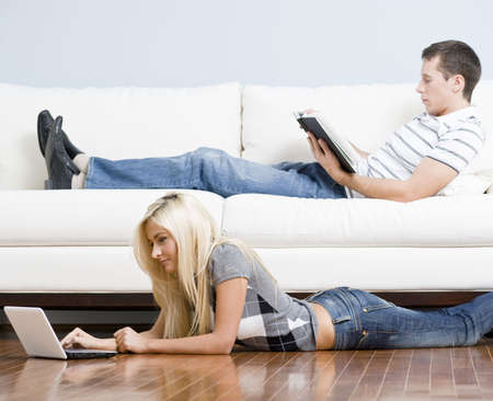 Man reads on a couch while woman stretches out on the floor with her laptop. Horizontal format. Stock Photo - 6249090