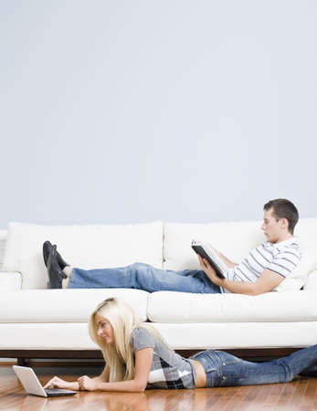 Man reads on a couch while woman stretches out on the floor with her laptop. Vertical format.