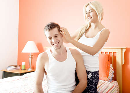 Woman ruffles man's hair as they relax in their bedroom. Horizontal format. photo