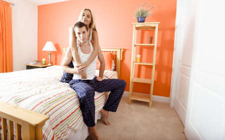 Smiling woman hugs man as they sit on their bed together. Horizontal format. photo