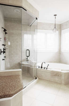 affluence: Upscale neutral-toned bathroom with jacuzzi tub and shower. Vertical format. Stock Photo
