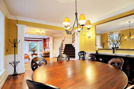 Wide-angle view of dining room, with round table and chandelier. Horizontal format.