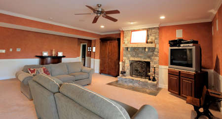 ceiling fan: Wide angle view of a family room, with ceiling fan, couches, and fireplace. Horizontal format.