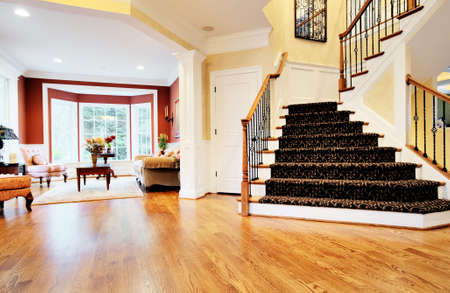 Open entryway with wood floor and staircase, with view of living room. Horizontal format. Stock Photo