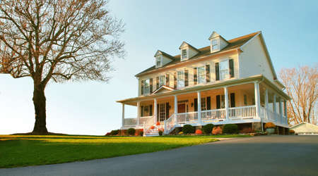 front house: Low angle view of a traditional upscale home with a single tree in the front yard. Horizontal format.
