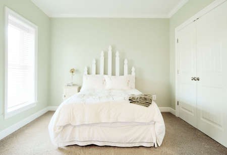 View of a simple upscale bedroom, decorated in light neutral shades. Horizontal format.
