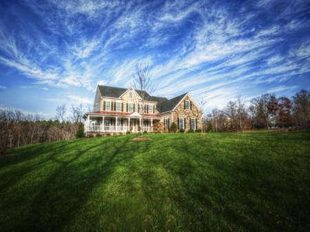 Brede hoek mening van een traditionele home en grote tuin, met blauwe hemel en cirrus wolken. Horizontale indeling.