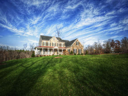 Wide angle view of a traditional home and large yard, with blue sky and cirrus clouds. Horizontal format.