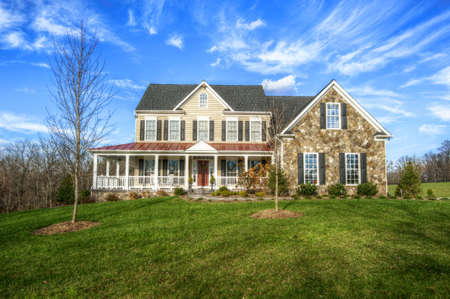 upscale: Traditional home and large yard, with blue sky and cirrus clouds. Horizontal format.