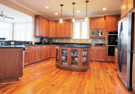 View of a large upscale kitchen with hardwood floors and modern fixtures. Horizontal format.