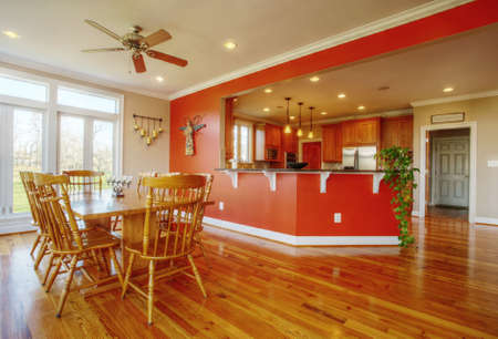 View of a homes dining area with hardwood floors. A kitchen is in the background. Horizontal format. photo